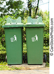 A green plastic garbage bin , great for recycling concepts and designs.