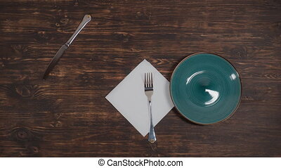 A green plate moves on the table with cutlery.