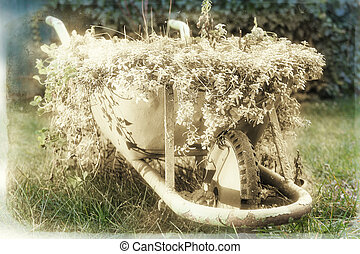 A green rustic wheelbarrow full of colorful flowers on a grass lawn old sepia variant