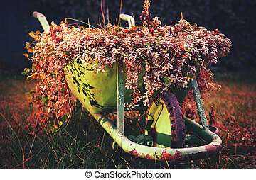 A green rustic wheelbarrow full of colorful flowers on a grass lawn red variant