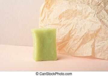 A green set of handmade soap on beige wrinkle paper background.
