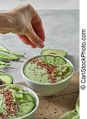 A green vegetable smoothie in a plate on a wooden board. A girl's hand puts flax seeds in a bowl. Healthy Eating