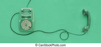 A green vintage dial telephone.