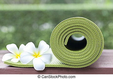 A green yoga mat and flowers