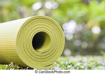 yoga mat - A green yoga mat sets on grass