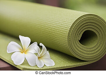 A green yoga mat sets on the floor