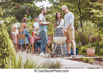 A grill party on the patio. Group of friends enjoying their time outside in the garden.