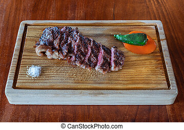 A grilled piece of fresh steak, chopped, lightly raw. On a texture board. Pepper sauce and salt, for the best taste.