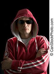 A grim looking Hoodlum wearing sunglasses