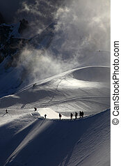 A group of alpinists on their way to the mont blanc at dawn.