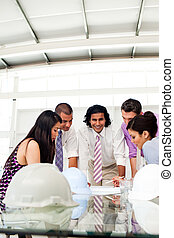 A group of architects and their manager discussing blueprints in a meeting