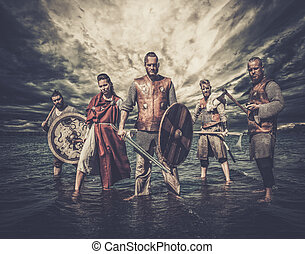 A group of armed Vikings, standing on the river shore.