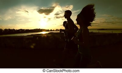 A group of athletes runners - two girls and a man running at city park, near river at sunset, silhouette, slow-motion