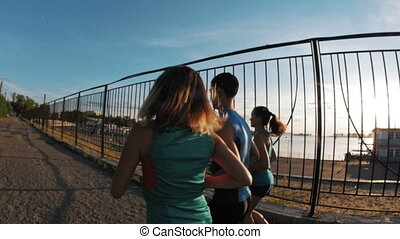 A group of athletes - two girls and a guy running at city park, near river at dusk, rear view, slow-motion