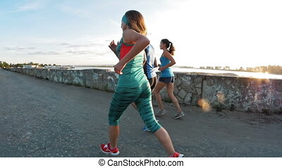 A group of athletes - two girls and a guy running at city park, near river at dusk, slow-motion