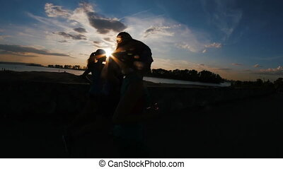 A group of athletes - two girls and a guy running at city park, near river at sunset, silhouette, slow-motion