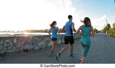 A group of athletes - two girls and a guy running at city park, near river at sunset, slow-motion