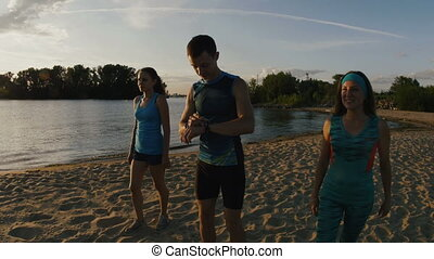 A group of athletes - two girls and a guy runs on beach,...