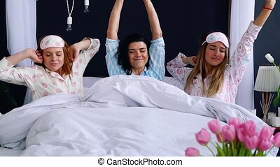 A group of beautiful girl wakes up in the morning in bed sipping after a bachelorette party in one bed in pajamas. Smile and laugh. Happy and carefree morning.
