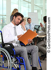 A group of business people in a meeting room, one of them in a wheelchair.