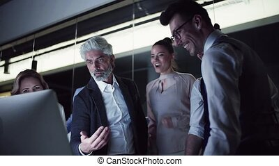 A group of business people with computer in an office,...