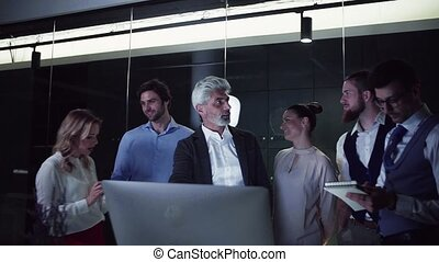 A group of business people with computer in an office, talking.