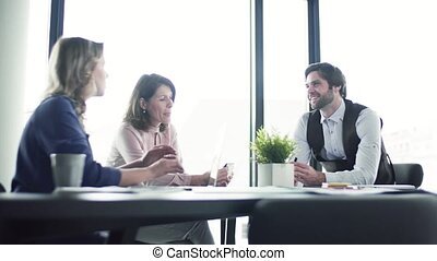 A group of business people with laptop sitting in an office, talking.