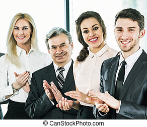 A group of businessmen rejoice at the success of the company with applause
