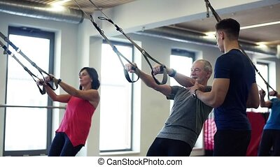 A group of cheerful seniors in gym with a young trainer doing exercise with TRX.