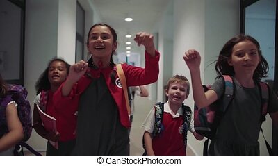 A group of cheerful small school kids in corridor, running. ...