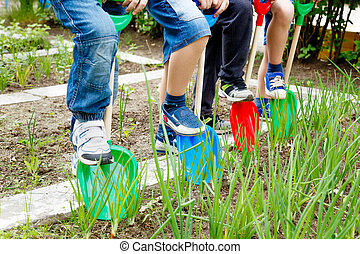A group of children play with plastic shovels in the garden ...