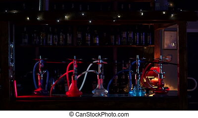 A group of colorful hookahs stands on the bar counter in a modern hookah bar.