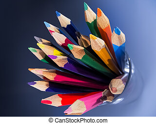 A group of coloured pencils in a glass tumbler