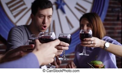 A group of cute young people in a modern restaurant at a table with snacks. Men and girls are baked with glasses of wine and shouting cheers. Friends celebrate a successful contract or birthday.