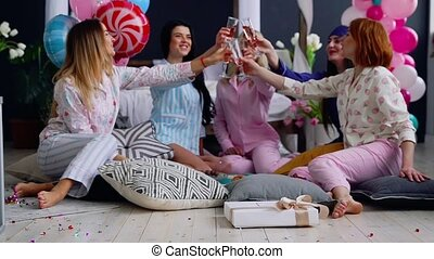 A group of dancing girls at a pajama party with glasses of...