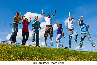 A group of diverse college students/friends jumping in the ...