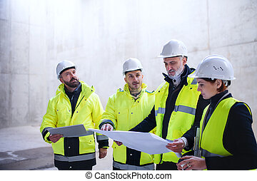 A group of engineers standing on construction site, holding blueprints.
