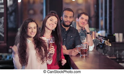 A group of friends at the bar with a beer smiling and showing thumb up