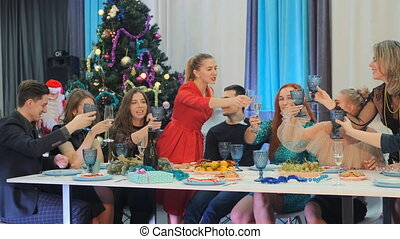 A group of friends at the table celebrates the new year