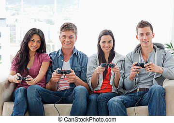 A group of friends play games while on the couch