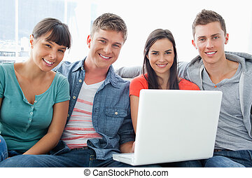 A group of friends sit on the couch together as they hold a laptop and look a the camera