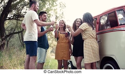A group of friends standing outdoors on a roadtrip through...