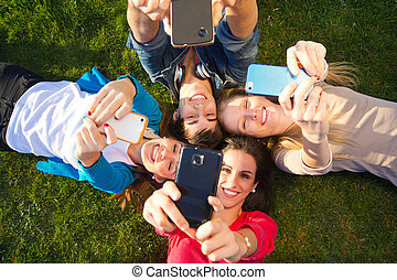 A group of friends taking photos with a smartphone - Outdoor...