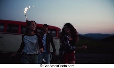 A group of friends with sparklers dancing outdoors at dusk....