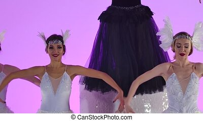 A group of gentle ballerinas in black and white tutus are dancing in the studio. Young women perform a theatrical show on a pink background. Close up. Slow motion