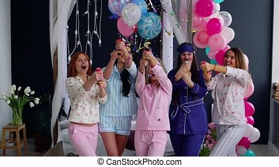 A group of girls laughing and smiling in pajamas launching...