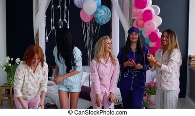 A group of girls laughing and smiling in pajamas launching confetti in slow motion 120 frames per second. Toss airbags shiny candies at a party