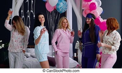 A group of girls laughing and smiling in pajamas launching confetti in slow motion 120 frames per second. Throw in the air shiny candy at the party. Pajama party before the wedding. Super slow motion.