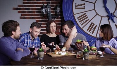 A group of grown-up friends who have not seen each other eat dinner in a restaurant, talking about the food they brought, friends like tasty snacks for red wine