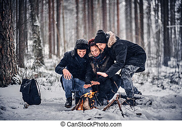 A group of happy friends staged a camping in the midst of a snowy forest